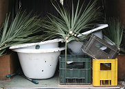Collecting discarded baths, beer crates and palm leaves for re-use.